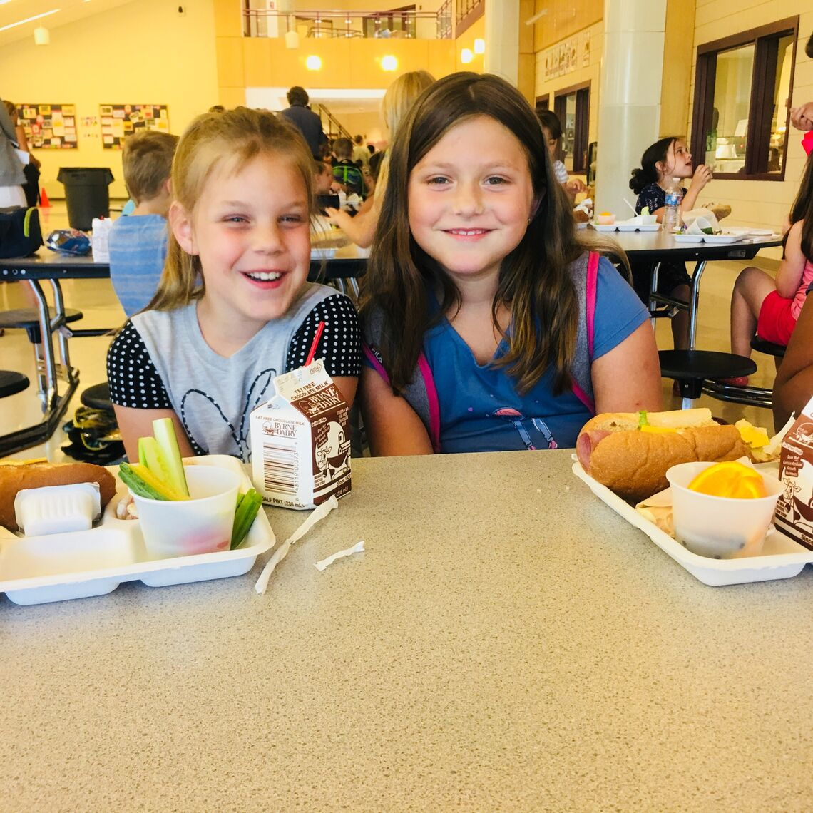 Two girls at a cafeteria table with their school lunch trays smiling