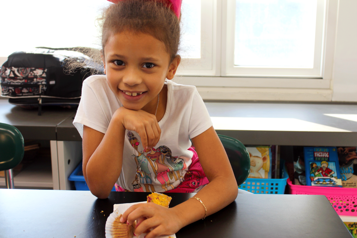 Elementary school student enjoys a morning muffin in the classroom at school