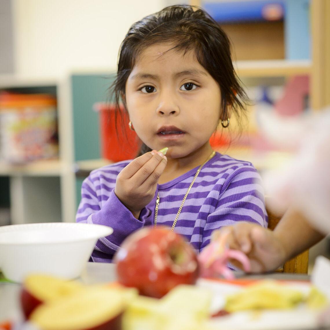 Kindergartener enjoys an apple at her desk