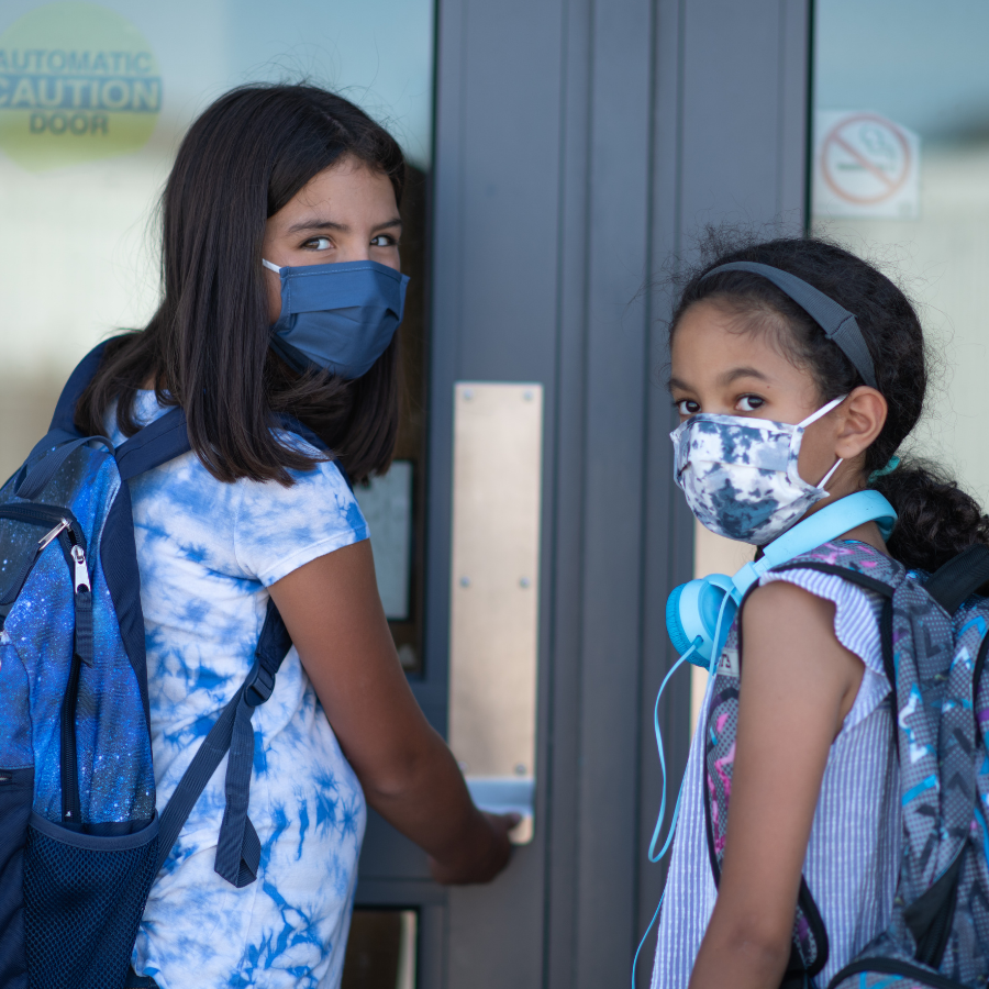 Two young girls with backpacks about to walk into school, turn to look back a the camera with masks on