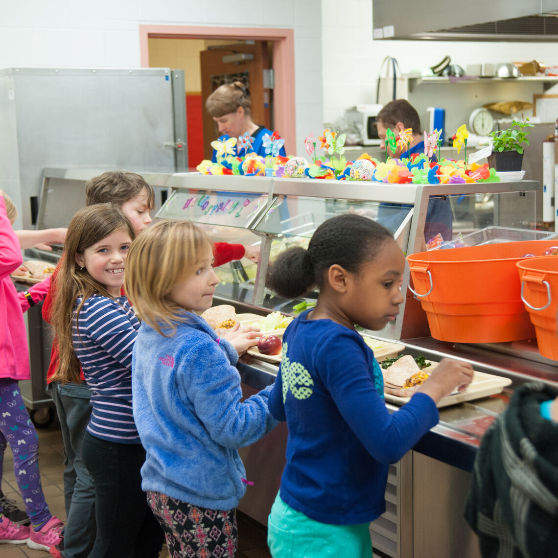 A group of students are lined up to get school lunch