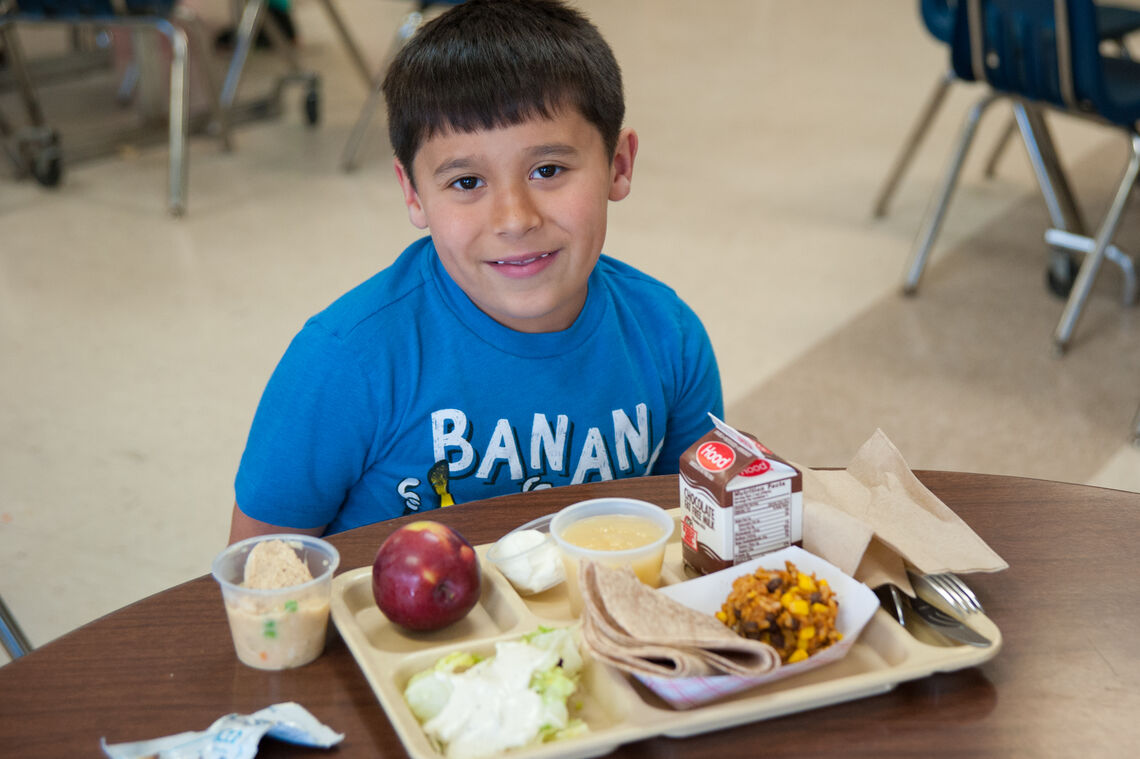Young Latino boy smiles with mixed rice and bean lunch at school cafeteria table