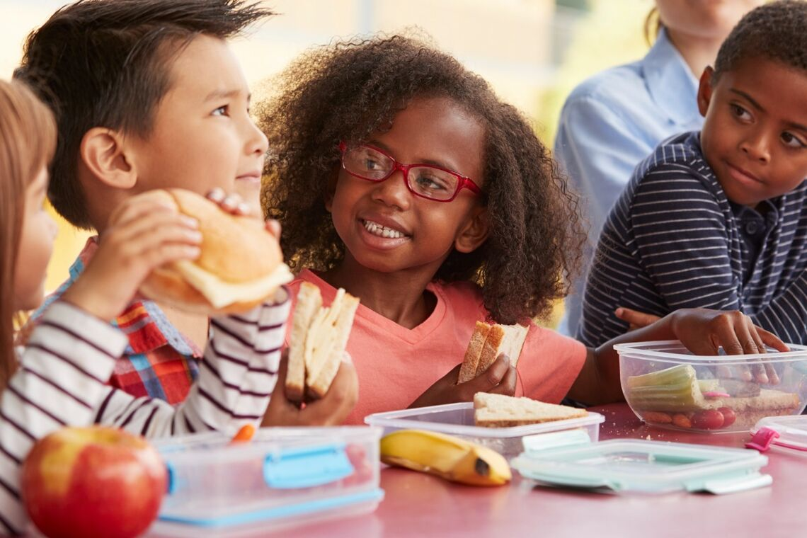 Racial and gender diverse group of kids eating school lunch.